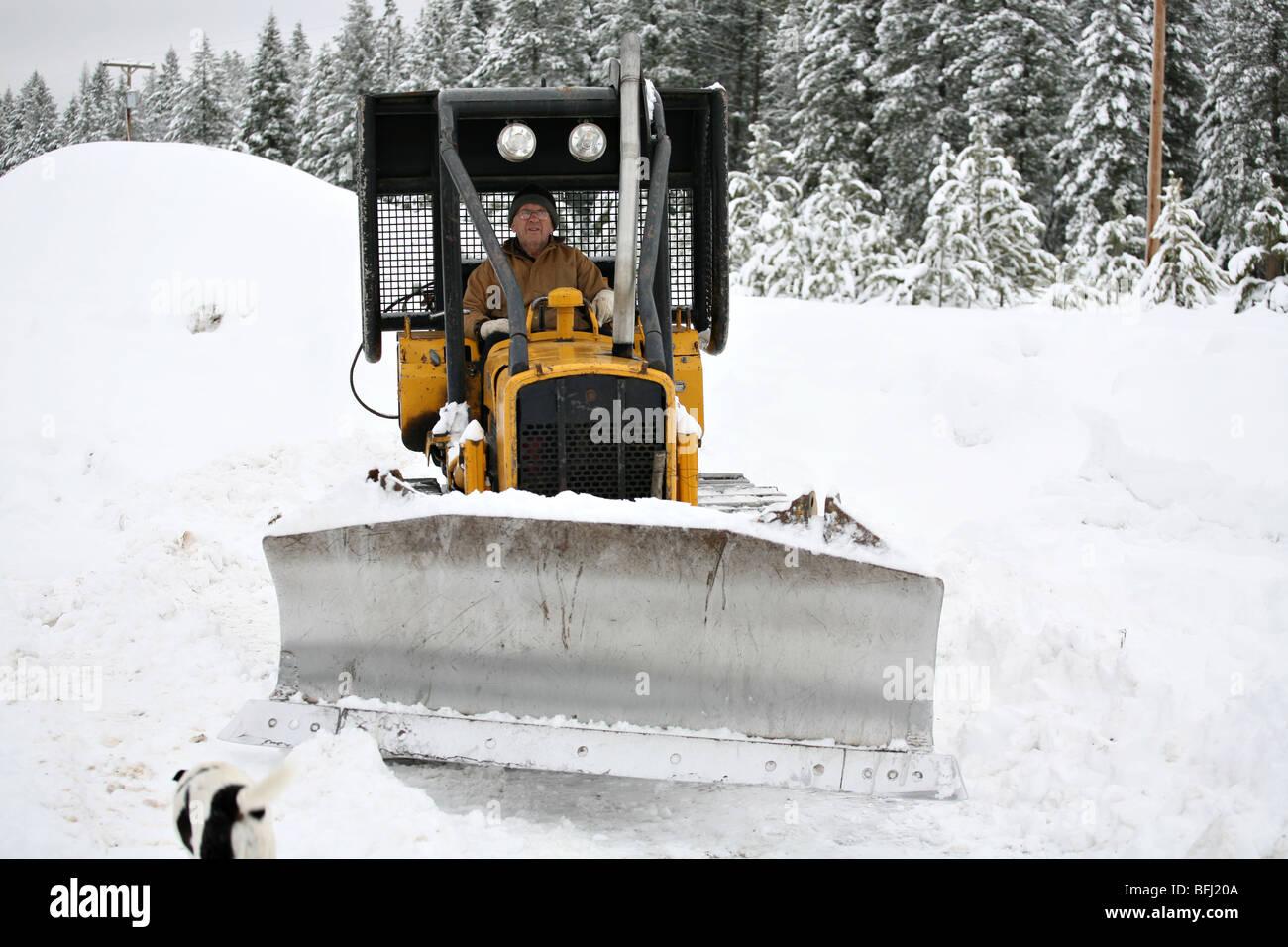 Senior citizen plowing snow in a bulldozer excavator. - Stock Image