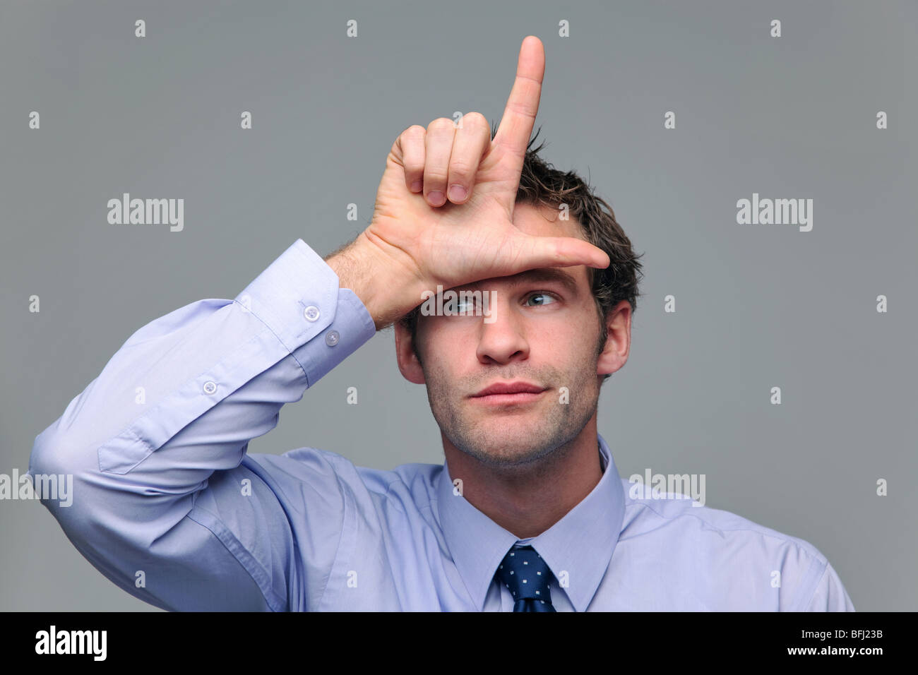Businessman making a loser gesture with his hand - Stock Image