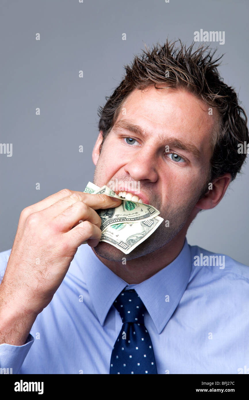 A businessman stuffing bank notes in his mouth. - Stock Image