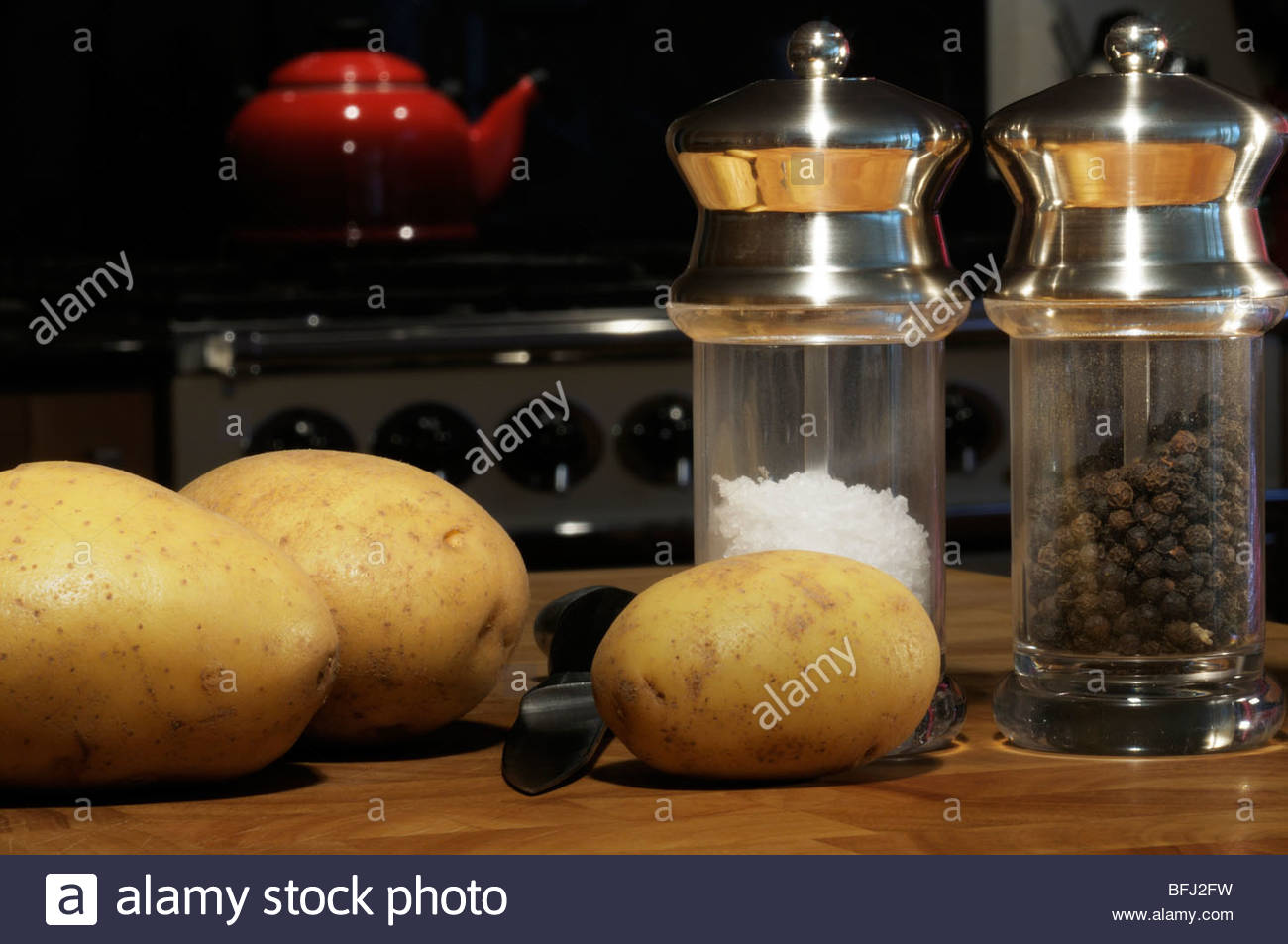Potatoes along with salt and pepper mills on a chopping board, Dorset, England, UK - Stock Image