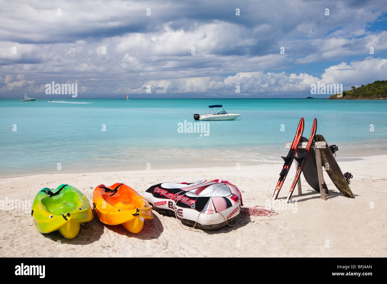 Water skis resting on a board and holiday styled kayaks, on the beach at Jolly Bay, Antigua, West Indies, Caribbean - Stock Image
