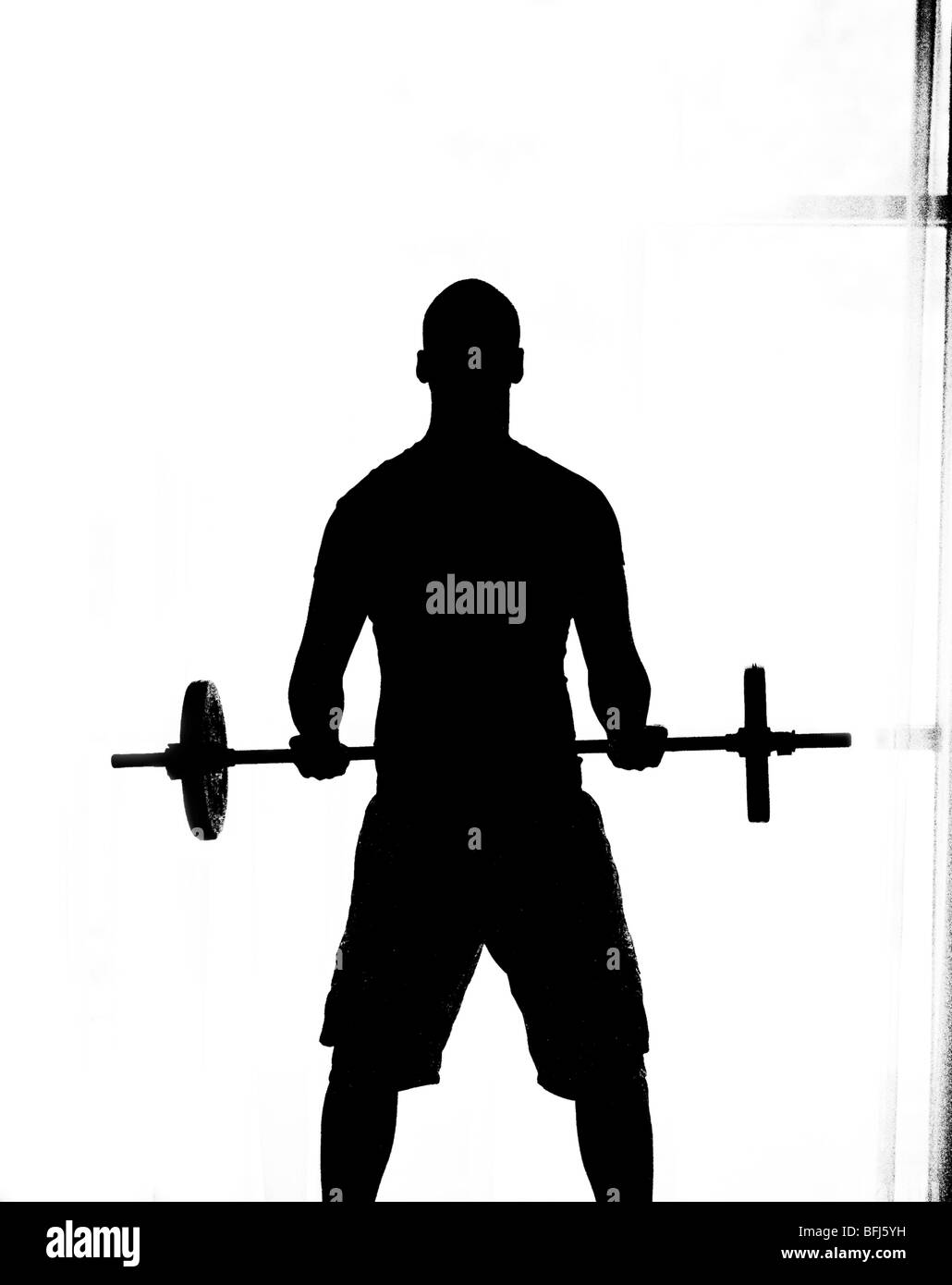 The silhouette of a man weight-lifting, Sweden. - Stock Image