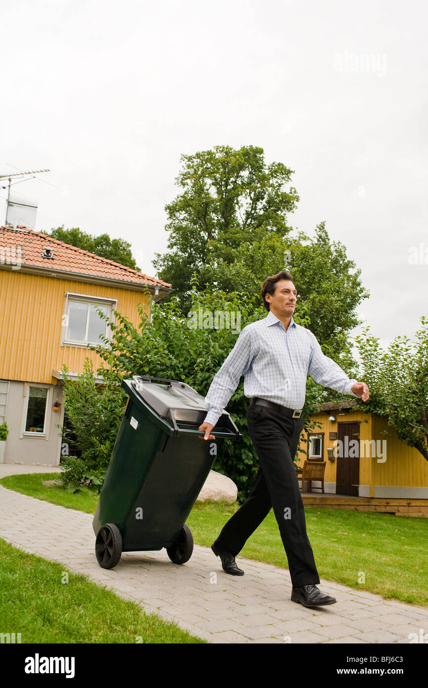 A man pulling a refuse bin, Sweden. - Stock Image