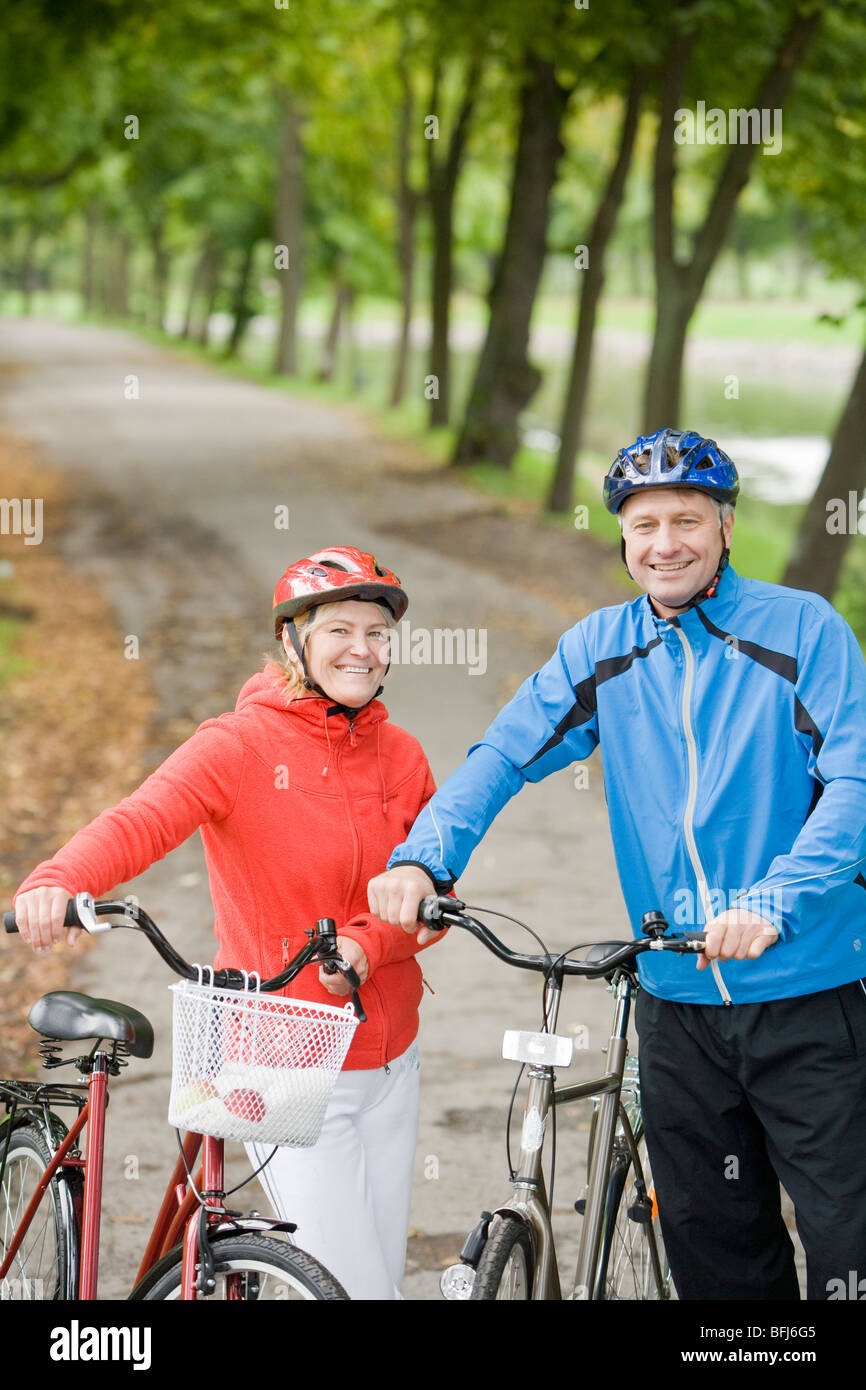 A couple cykling in a park, Sweden. - Stock Image