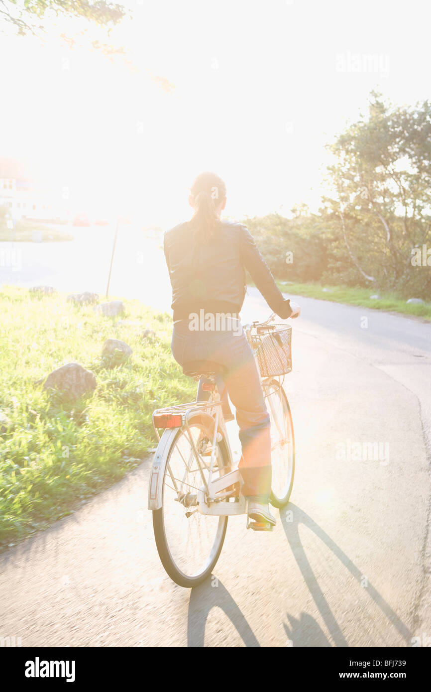 Woman riding a bike against the light, Sweden. - Stock Image