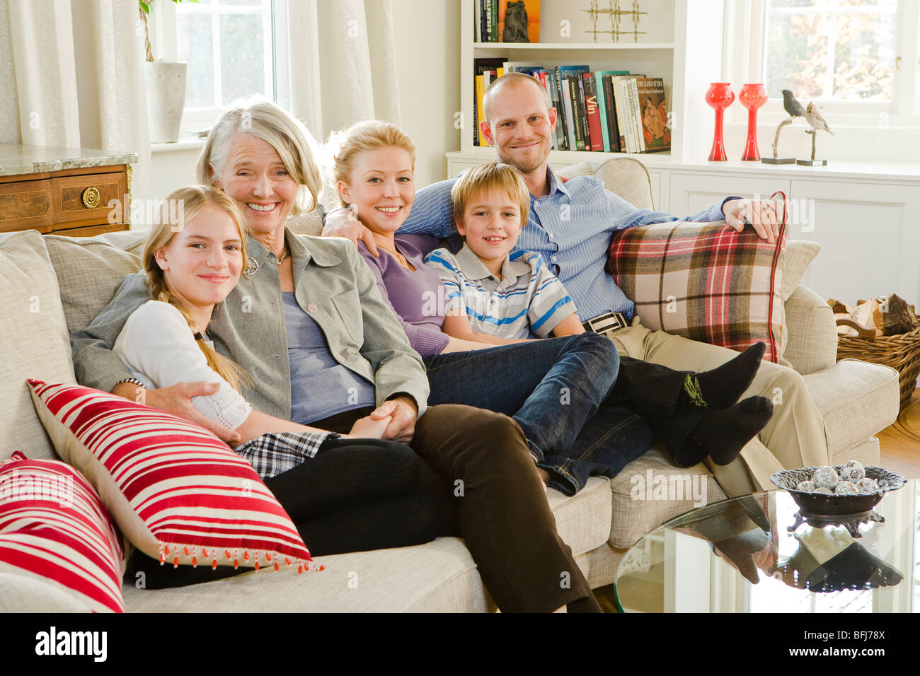 Multi-generation family sitting in a sofa, Sweden. - Stock Image