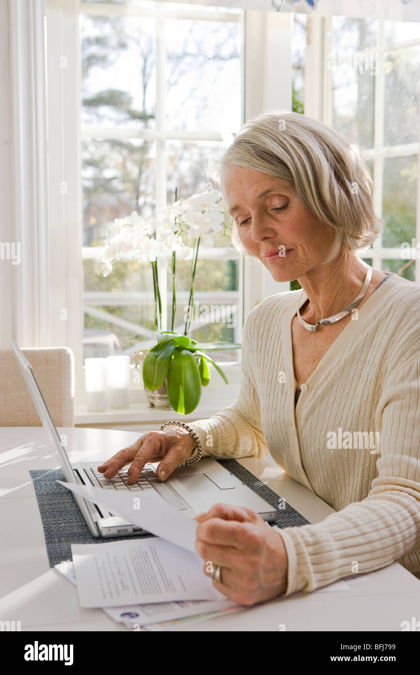 Senior woman using a laptop at home, Sweden. - Stock Image
