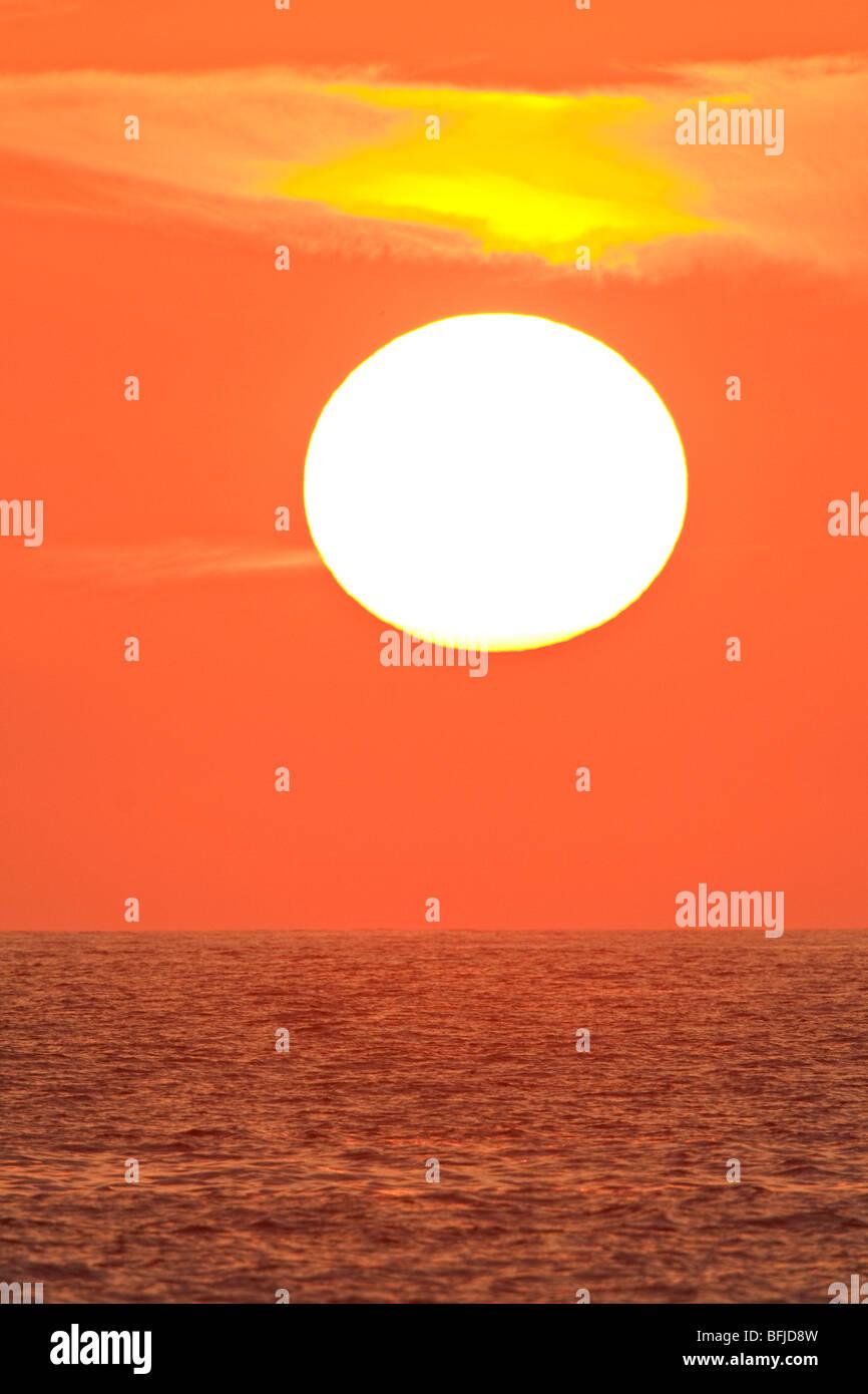 The sun sets over the Pacific Ocean along the coast of central Ecuador. - Stock Image