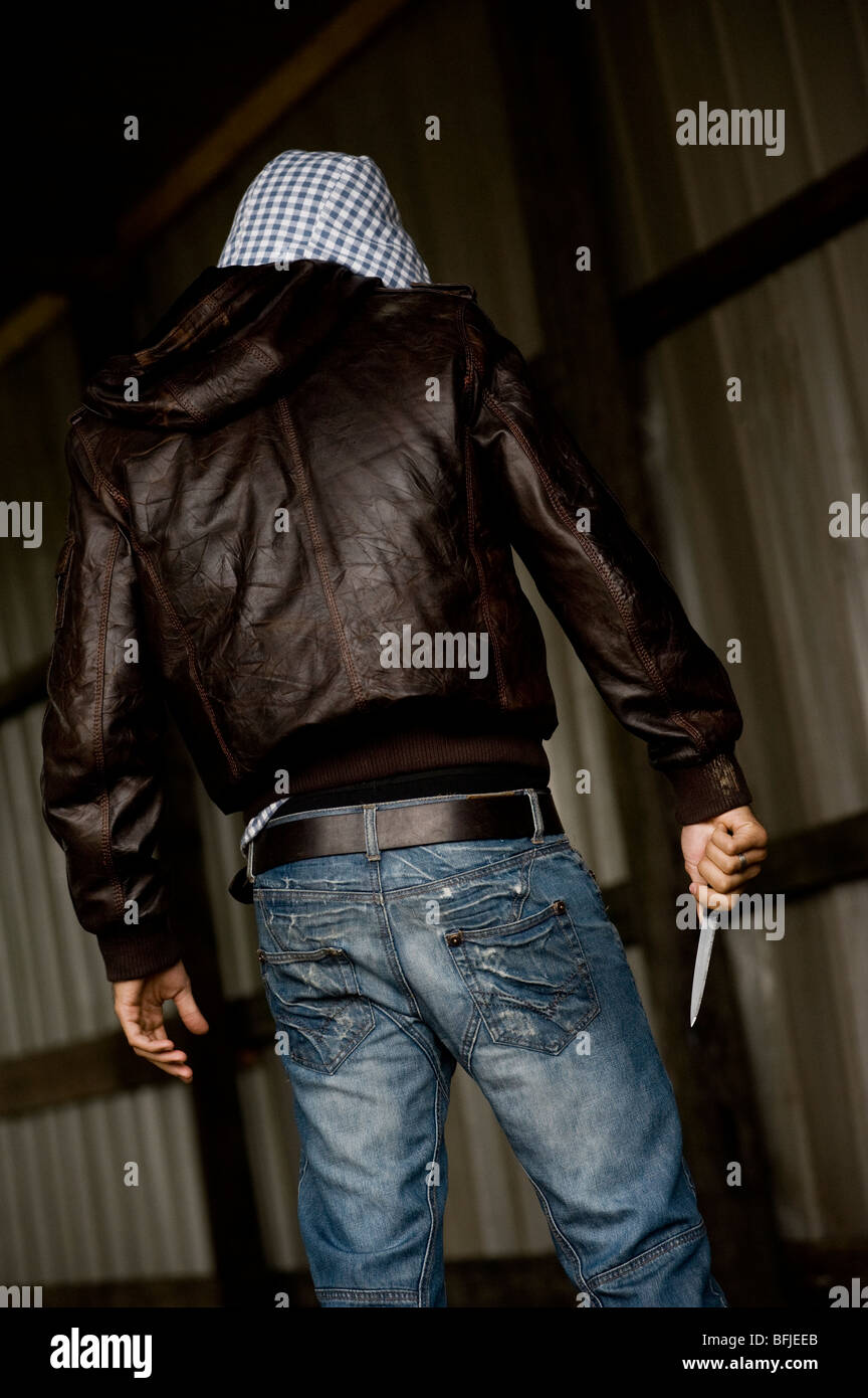 Rear view of a hooded man carrying a knife. - Stock Image