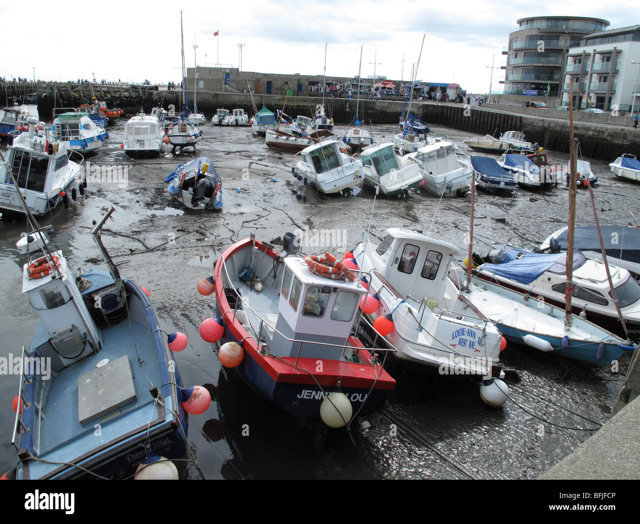 Small boats in the marina at West bay, Dorset at low tide in summer - Stock Image