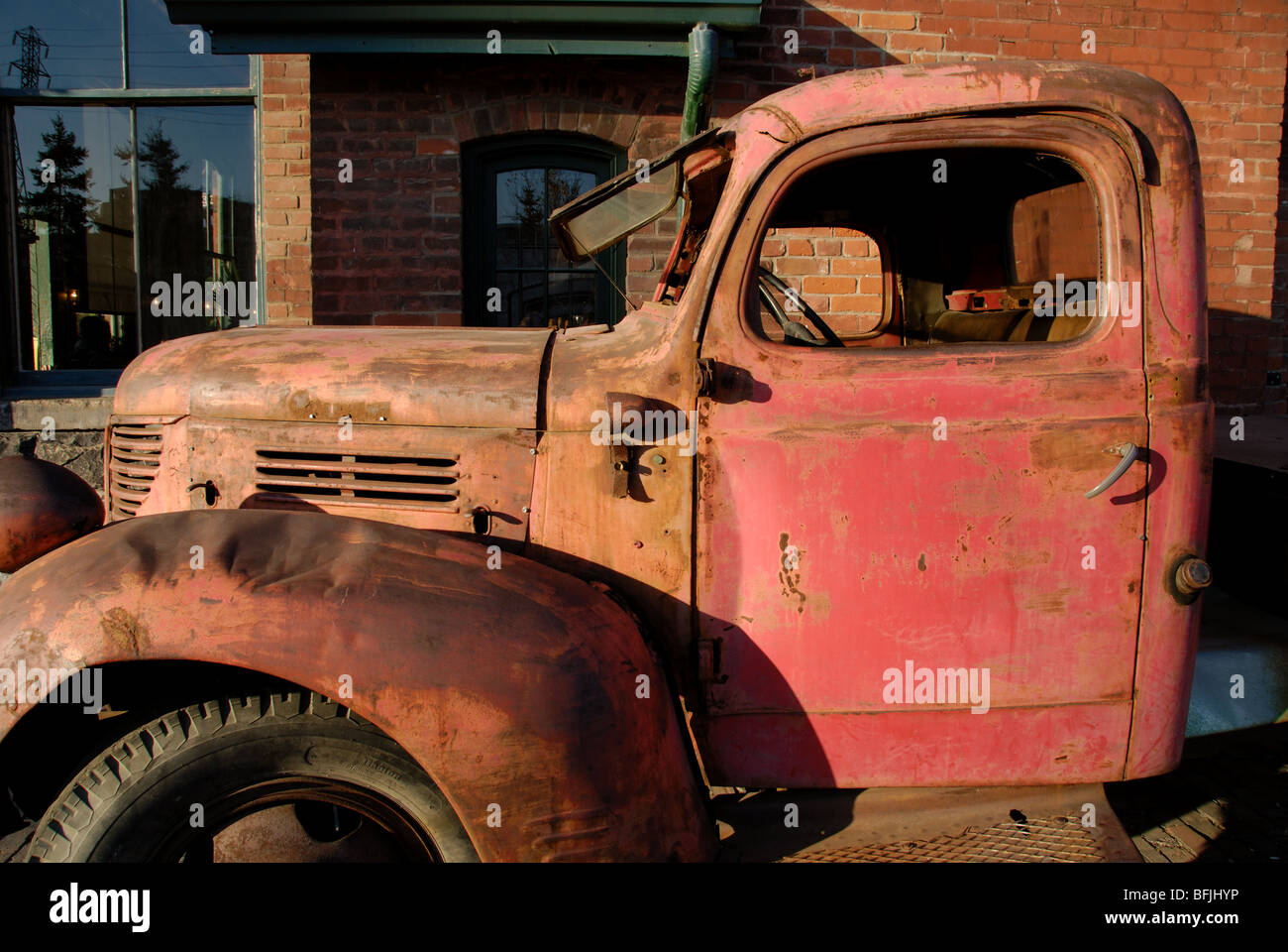 A Side View Of An Old Rusted And Abandoned Red 1947 Fargo Pickup Truck