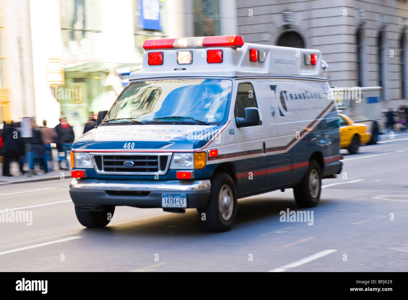 New York City , The Big Apple , Trans Care ambulance with lights flashing rushes to emergency in a blur - Stock Image