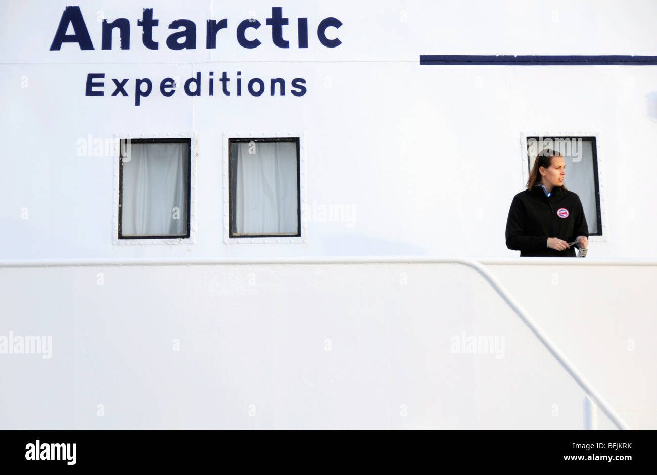 A female tourist standing on the deck of Antarctic expedition vessel the MV Ushuaia - Stock Image