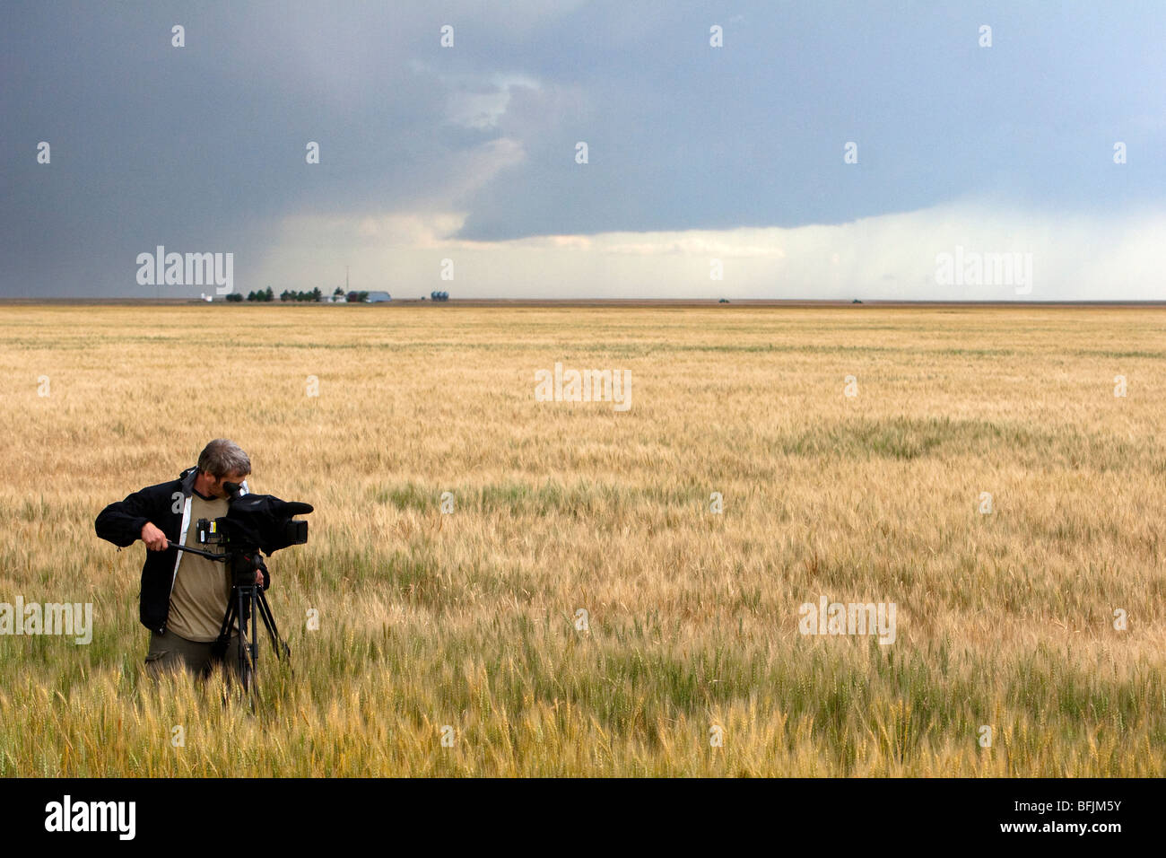 Cameraman Brain Pollack for the Weather Channel stands in prairie grass and films a developing storm, June 10, 2009. - Stock Image