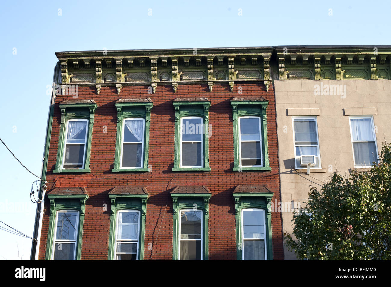 old brick building Red Hook elaborate carved wood window surrounds & cornice adjoins similar building altered - Stock Image