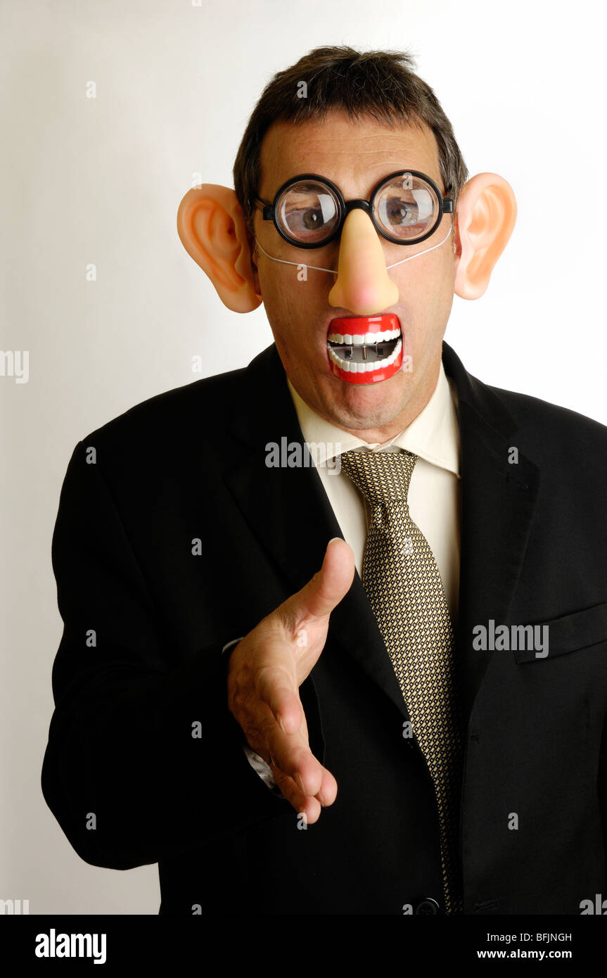 man in disguise holding out a hand for handshake - Stock Image