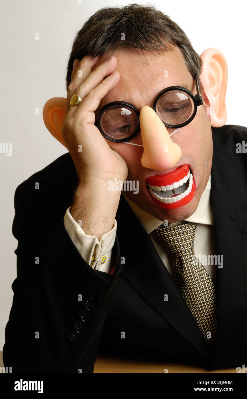 man in disguise leaning head on hand - Stock Image