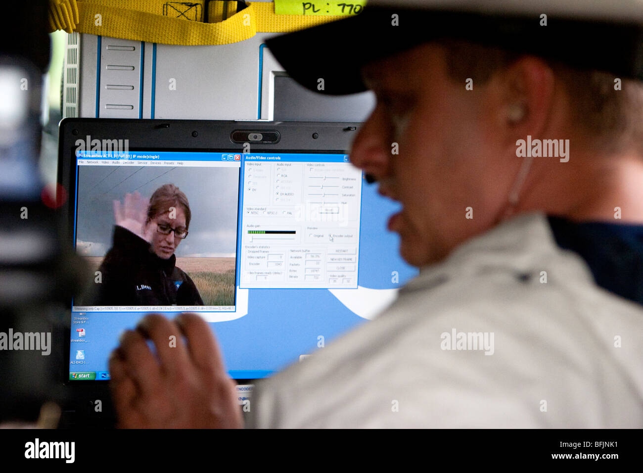 A weather channel production assistant assists reporter Katy Tur with a live streaming broadcast from western Kansas, - Stock Image