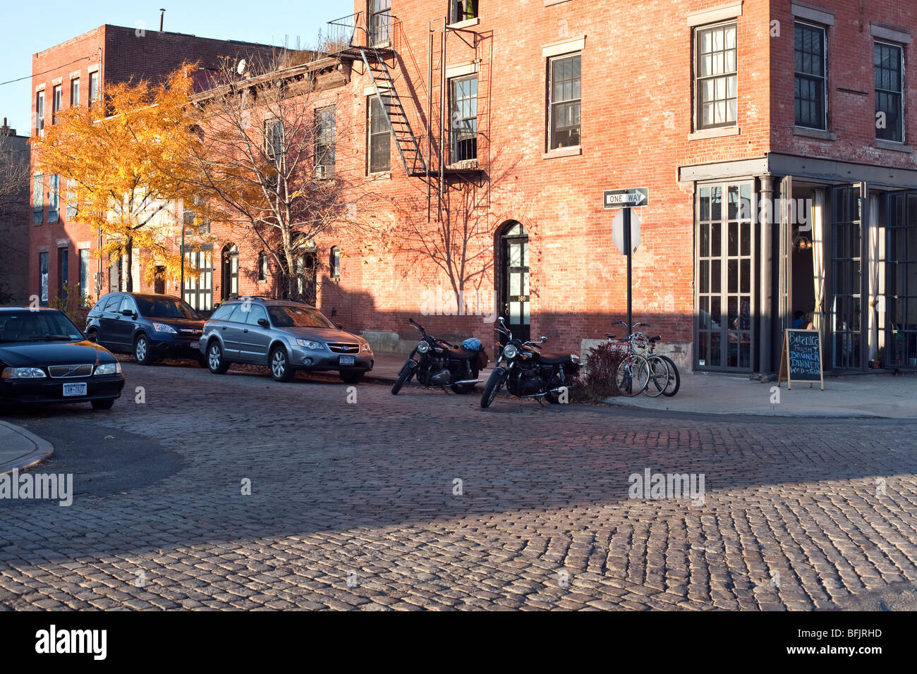 cobblestone intersection & charming restored red brick buildings with corner bistro in a quiet gentrified area of Stock Photo