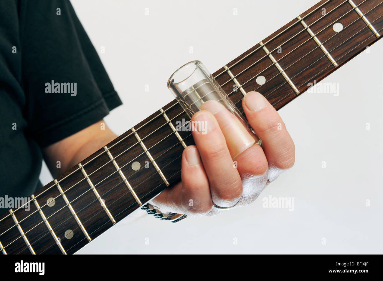 a mans hand demonstrates a bottle neck glass guitar slide against a guitar neck - Stock Image
