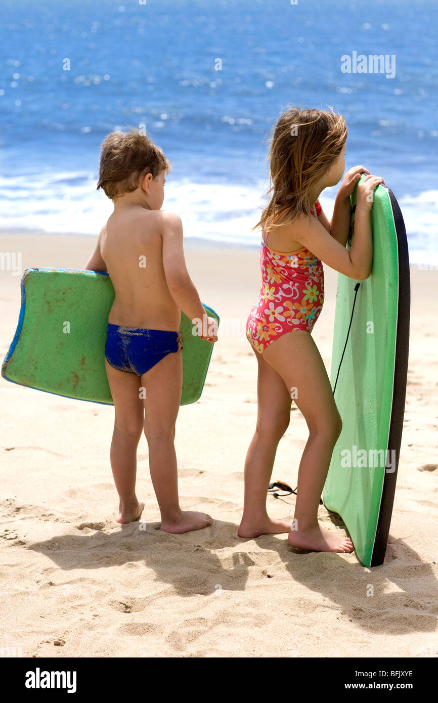 Two children on the beach looking at the sea, Brazil. - Stock Image