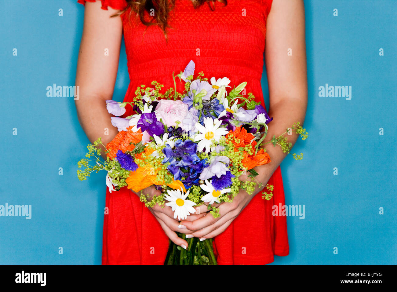 Girl in a red dress holding flowers. - Stock Image