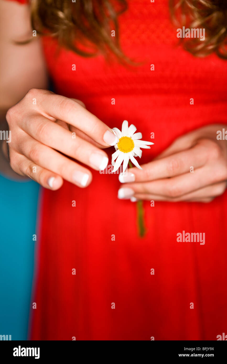 Girl in a red dress holding a flower. - Stock Image