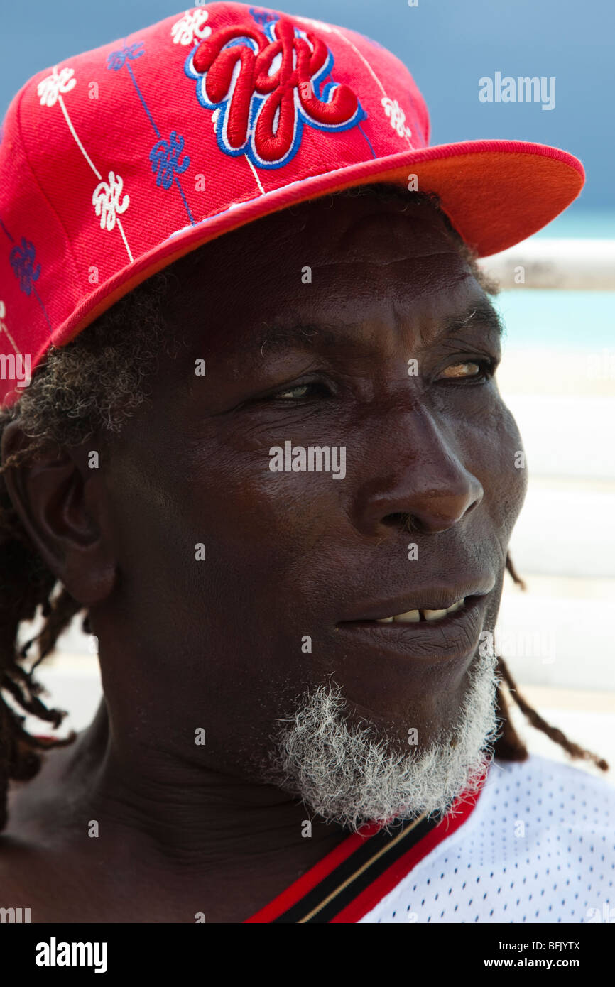 Black man from Antigua wearing a red baseball hat and working on the beach - Stock Image