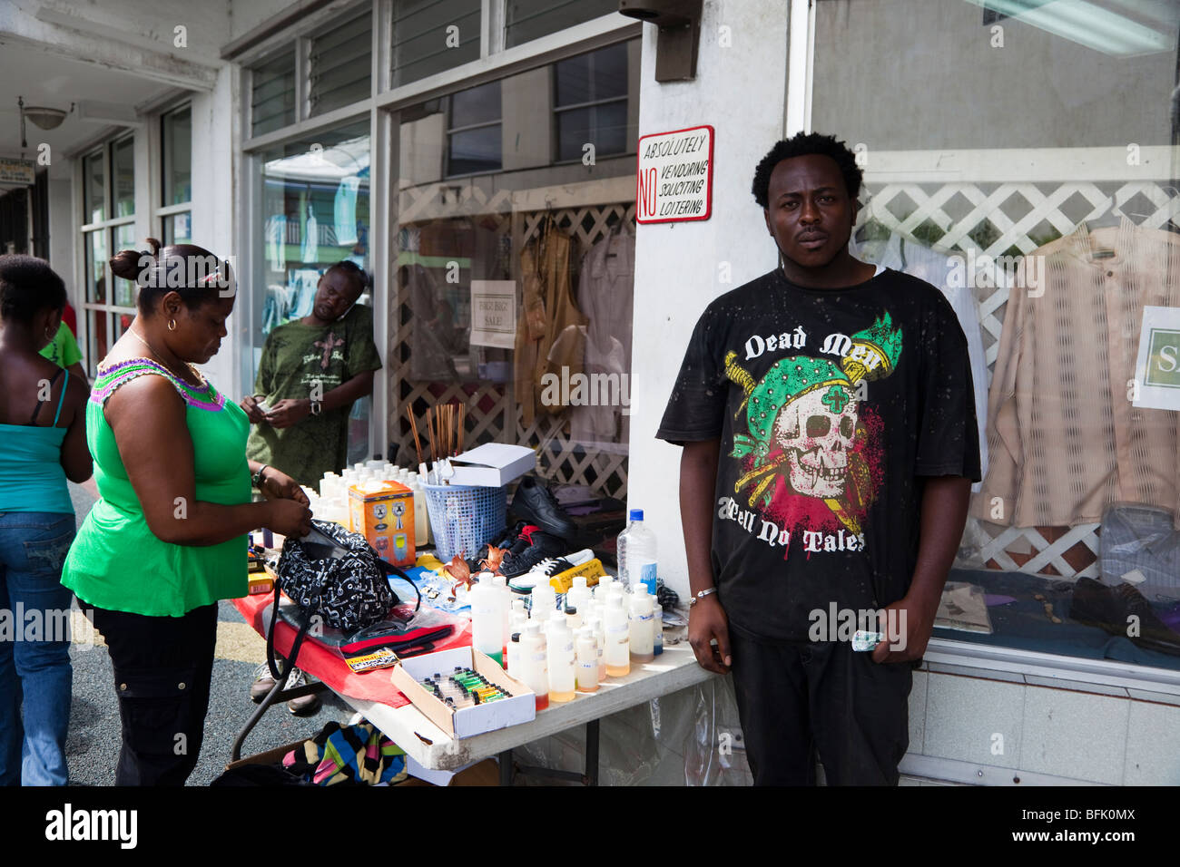 Black man from Antigua selling household goods from a stall at a street corner in St Johns town. Stock Photo