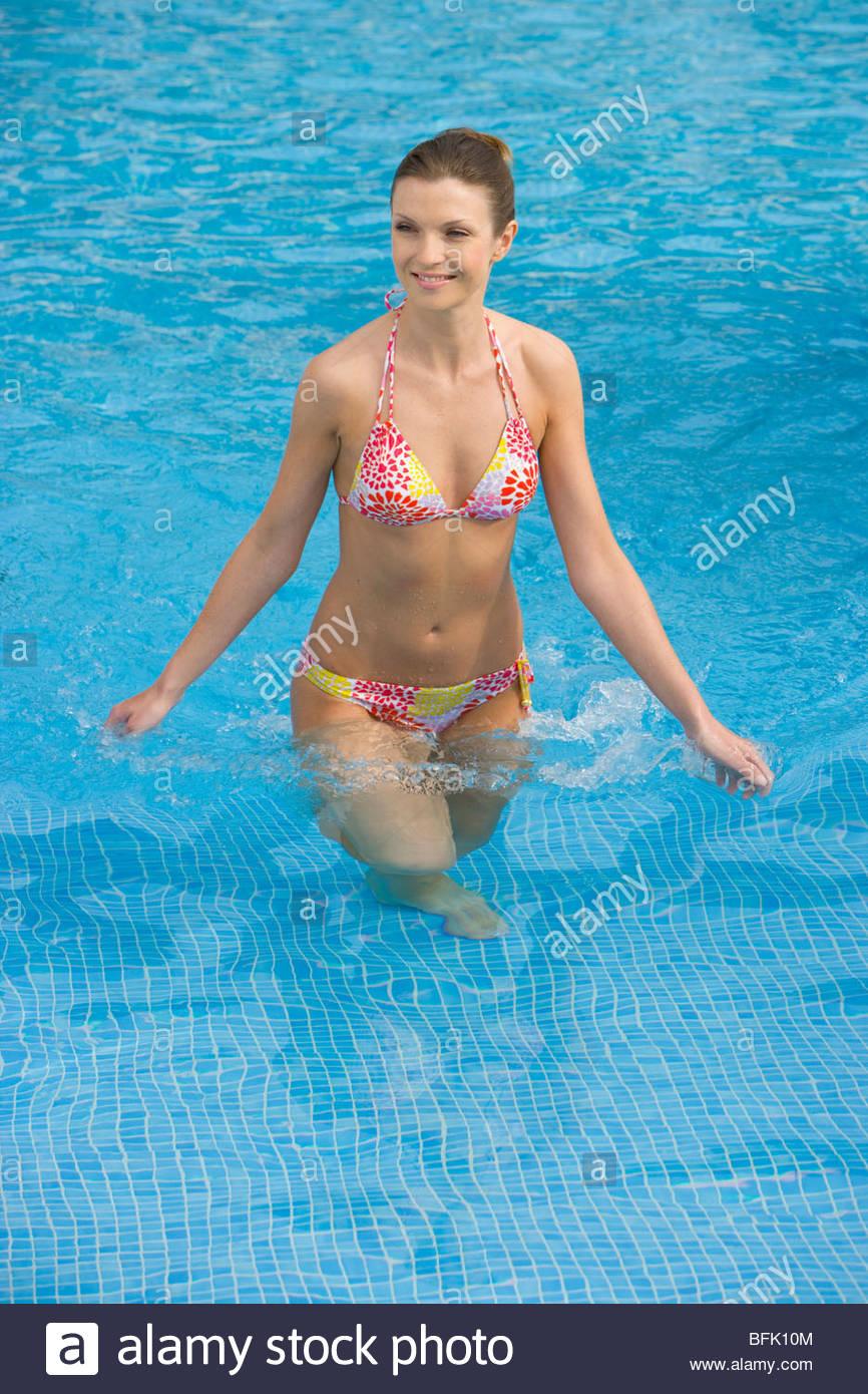 Smiling woman in bikini standing in swimming pool - Stock Image