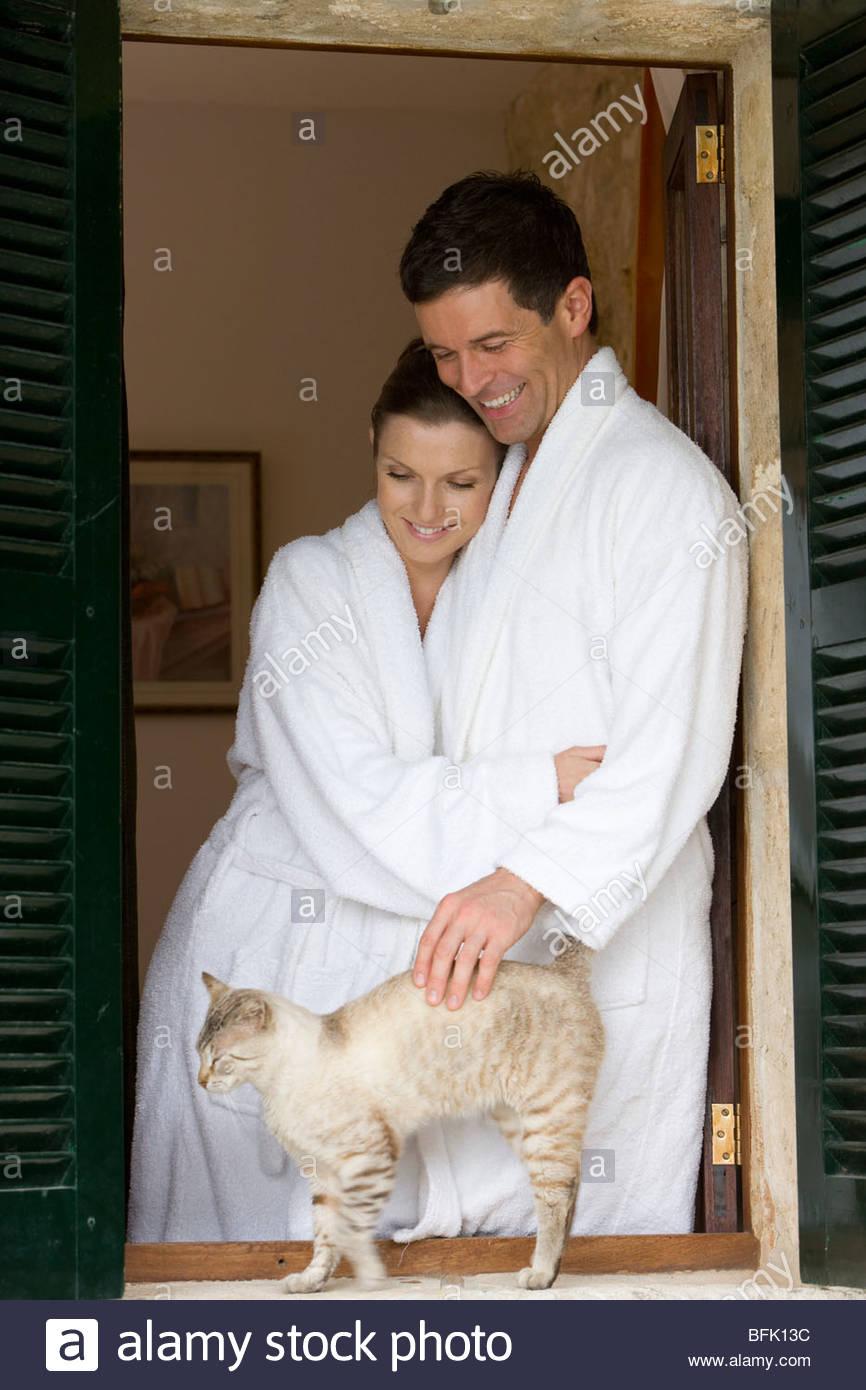 Couple in bathrobes petting cat on windowsill - Stock Image