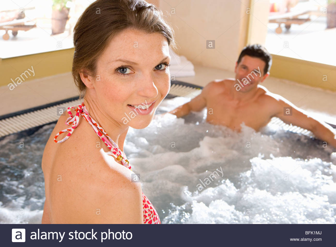 Smiling couple in hot tub - Stock Image