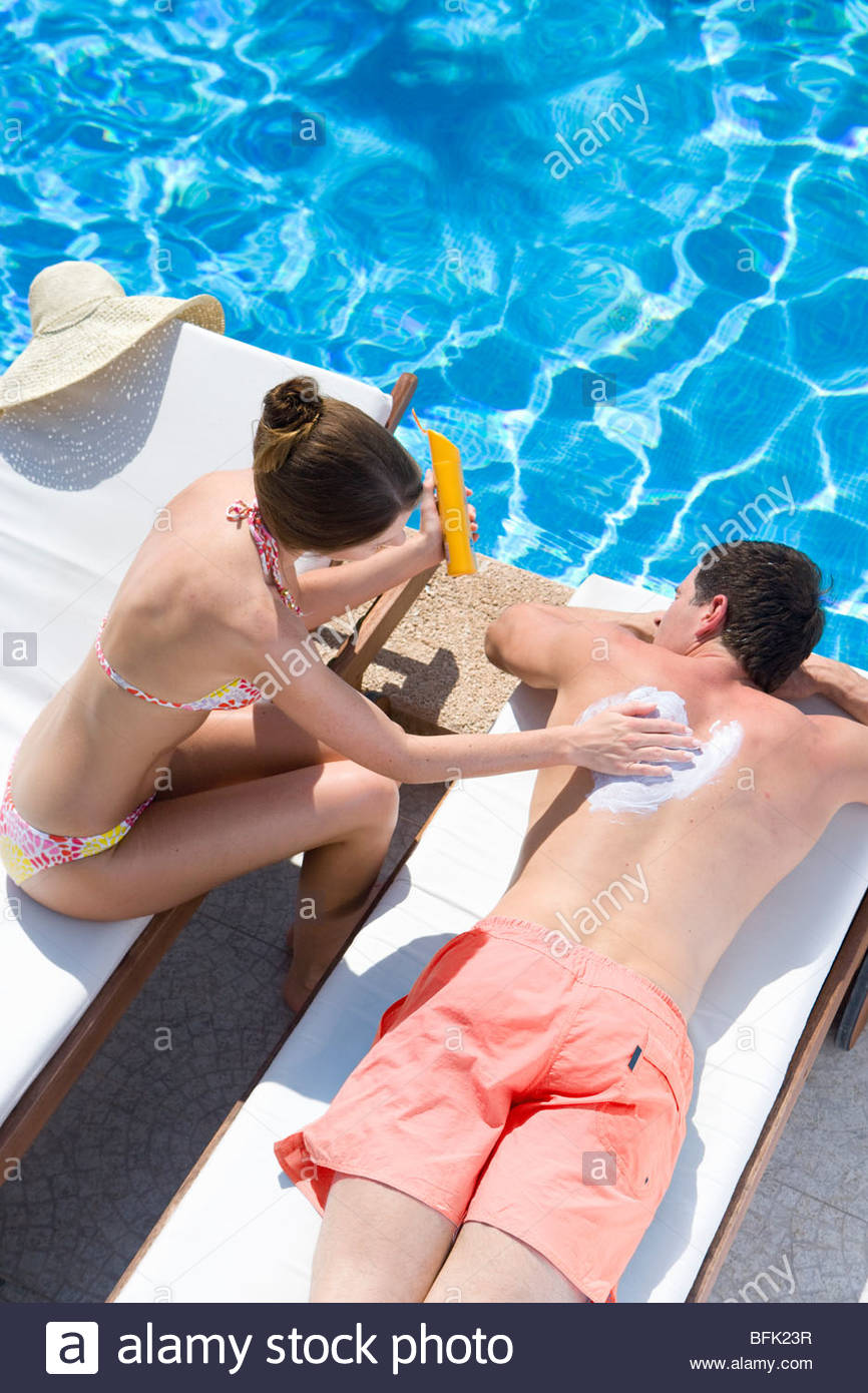 Woman applying sunscreen to man's back at poolside - Stock Image