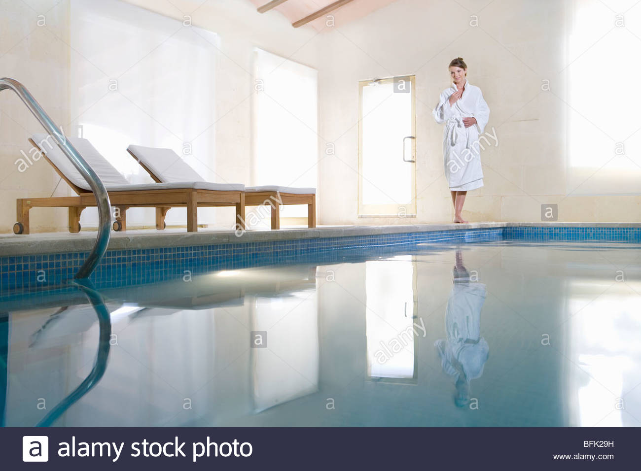 Woman in bathrobe standing at poolside - Stock Image