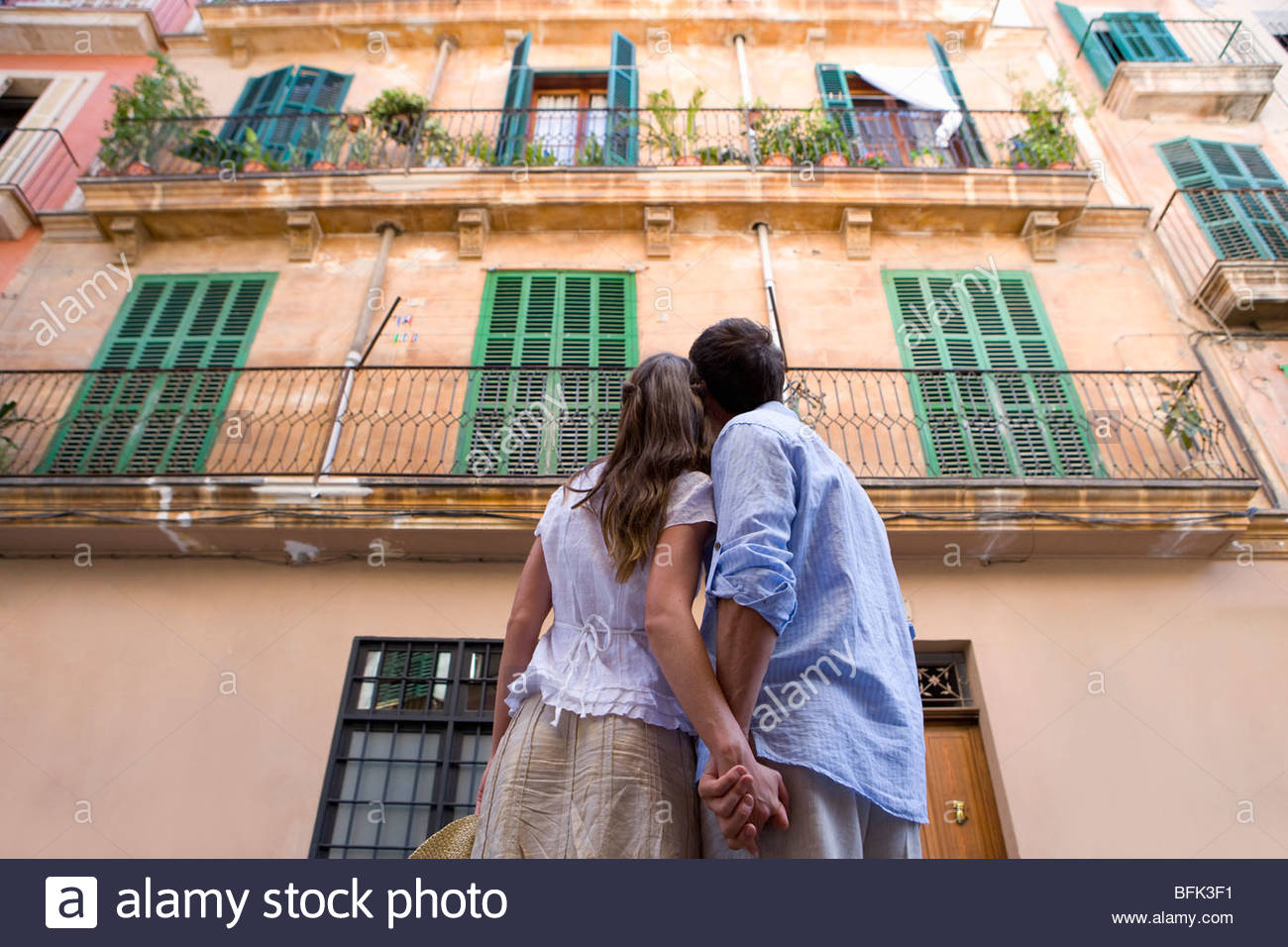 Couple holding hands and looking up at building - Stock Image