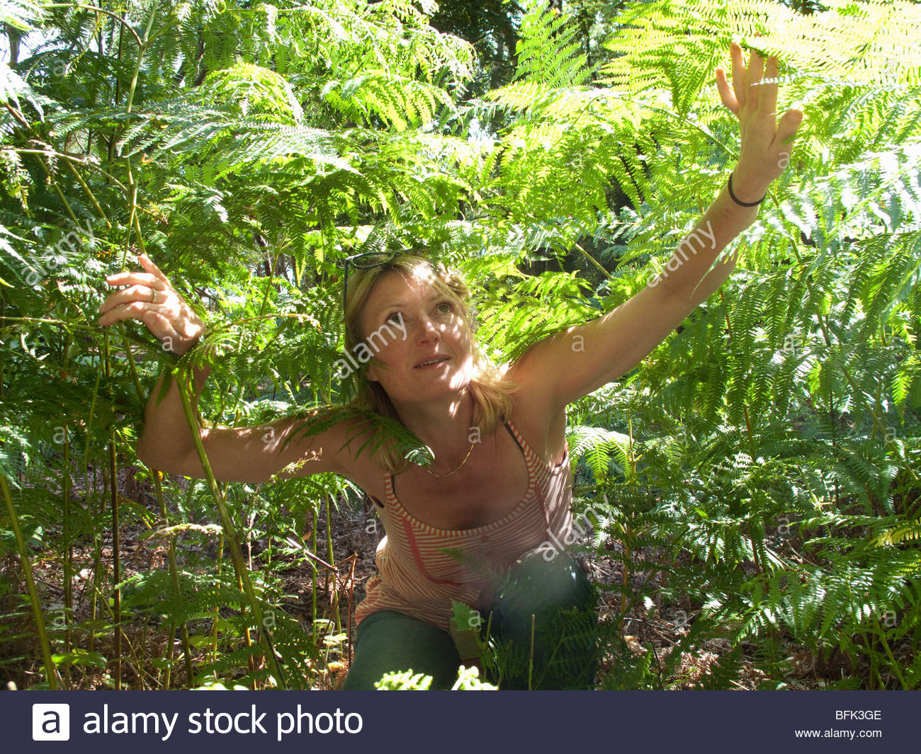 Woman crouching among plants in forest and looking up - Stock Image