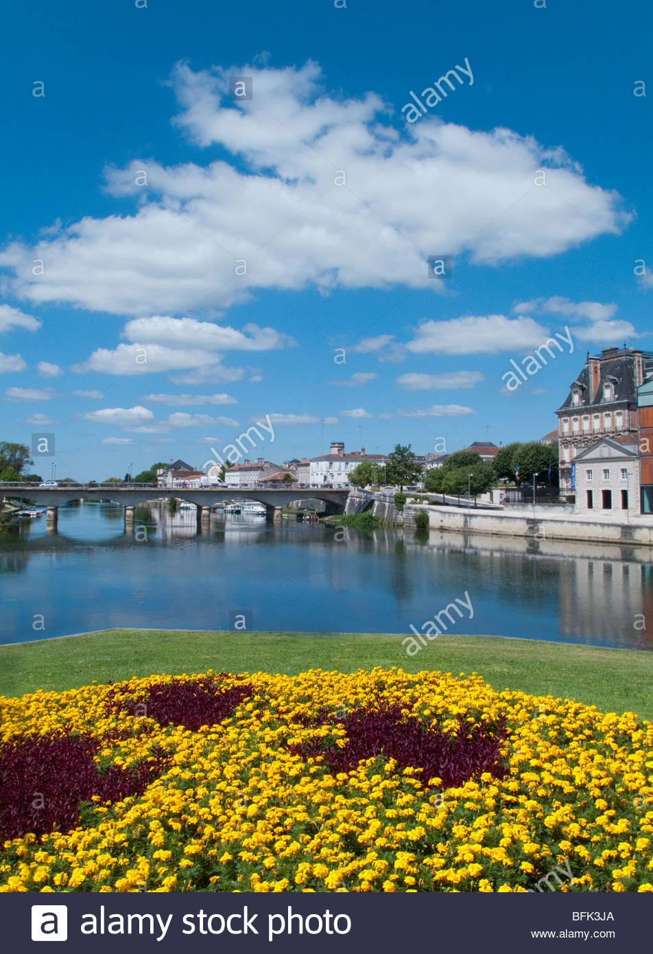 View of town and bridge spanning river on sunny day Stock Photo