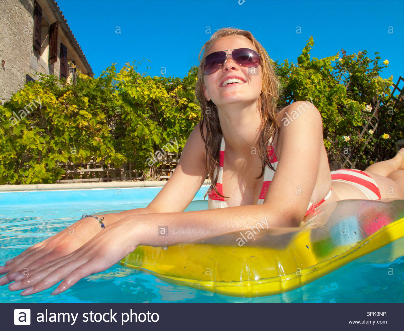Smiling teenage girl laying on pool raft and looking up in swimming ...