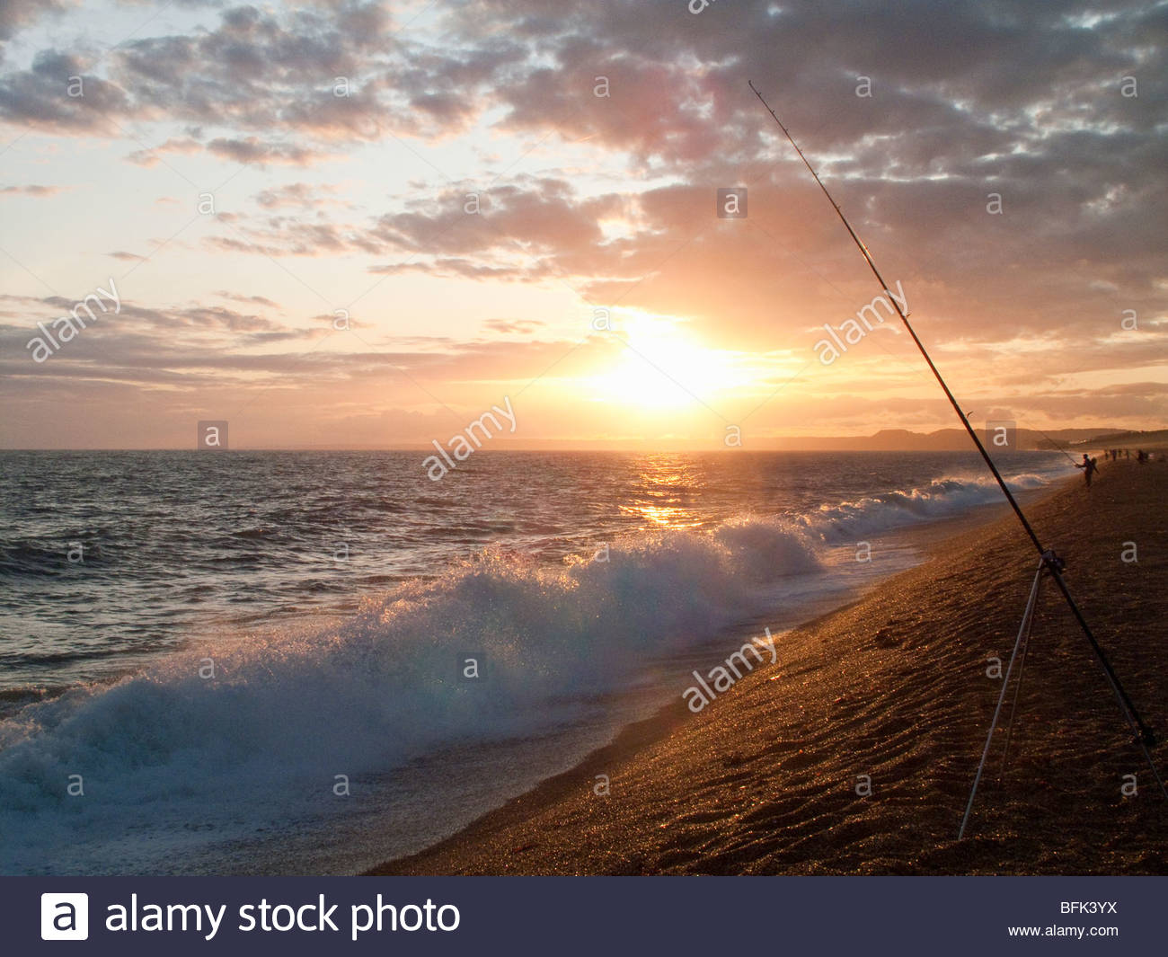Tranquil sun setting on horizon over ocean with fishing rod in foreground - Stock Image