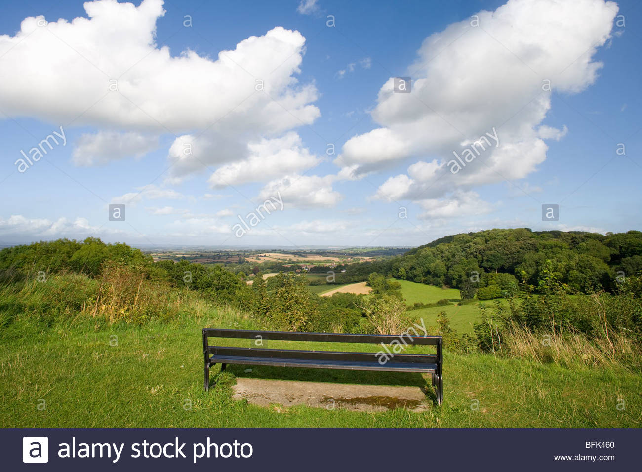Bench on hill overlooking scenic view of countryside - Stock Image