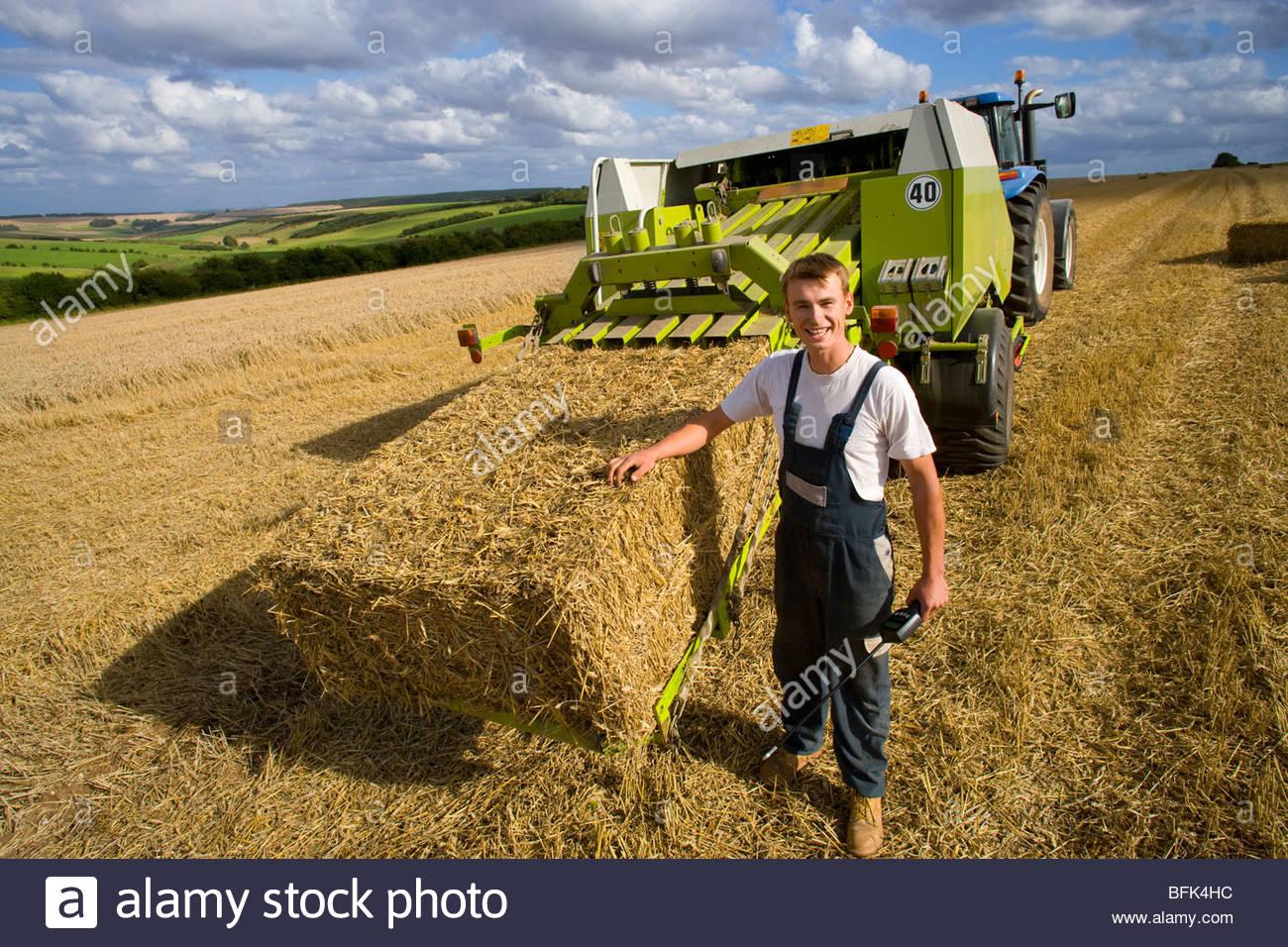 Farmer holding moisture reading equipment next to straw bale on baler in rural field - Stock Image