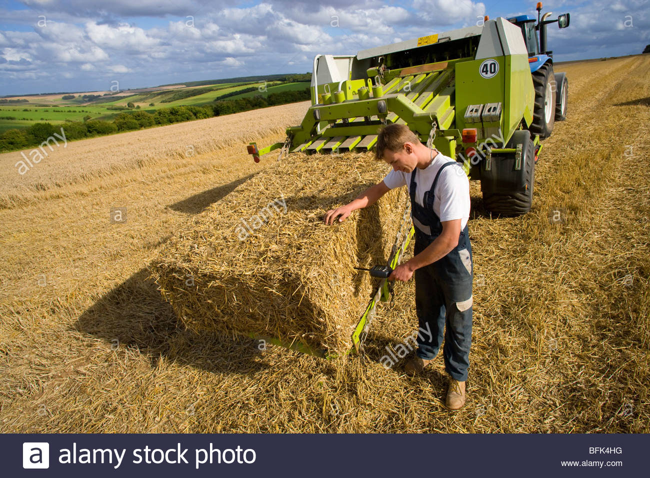 Farmer examining straw bale on baler with moisture reading equipment in rural field - Stock Image