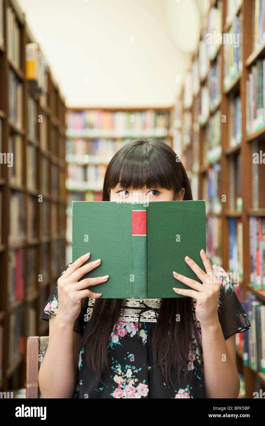 Asian woman reading book in library Stock Photo