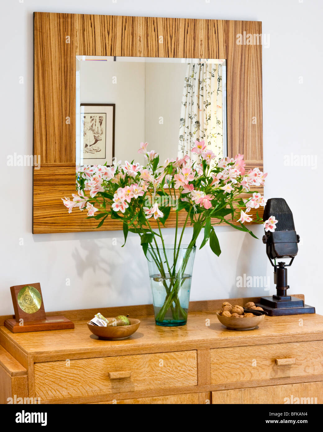 Sideboard with AXBT microphone and vase of flowers in a typical English dining room - Stock Image