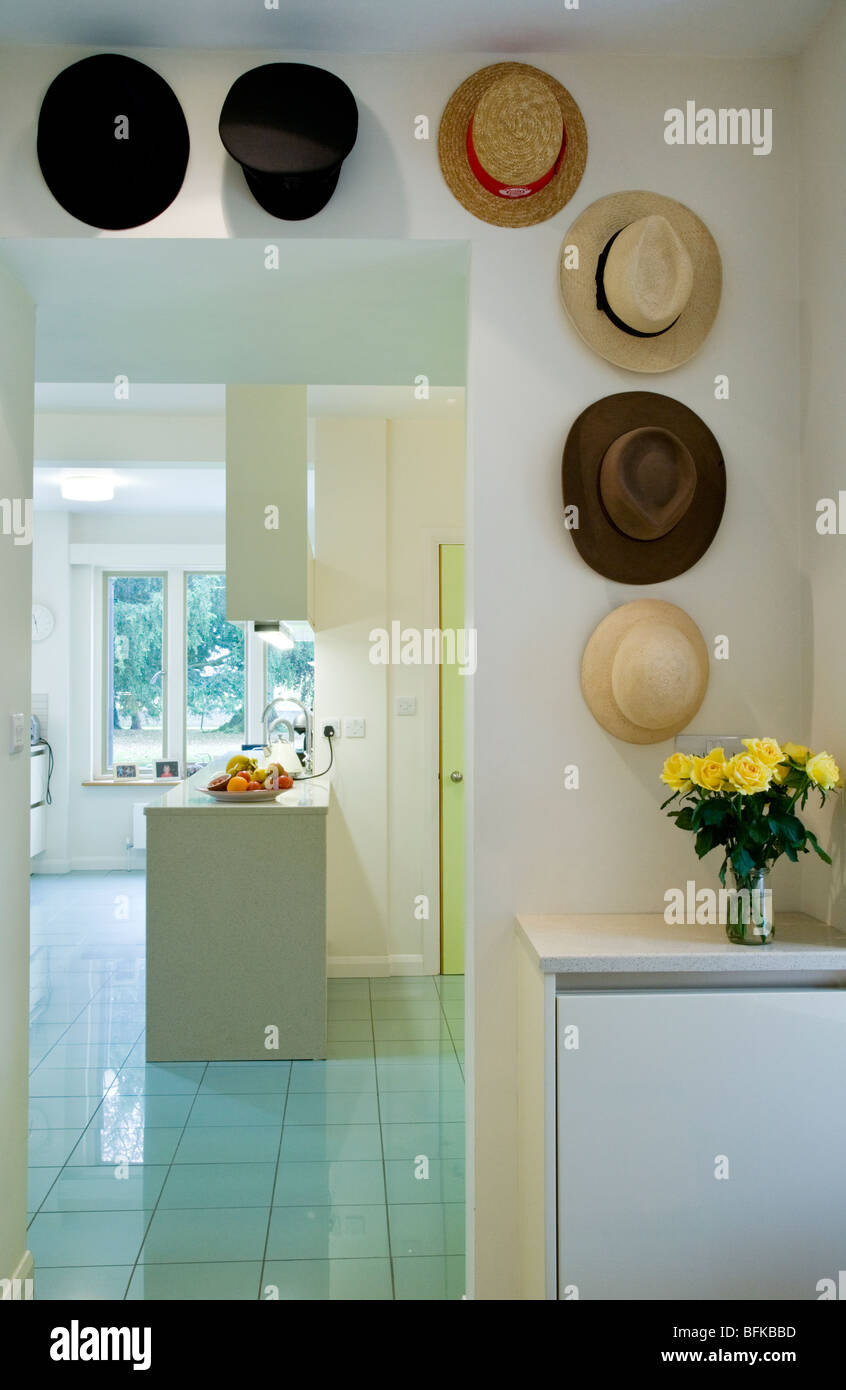 View through doorway decorated with hats into a modern contemporary light and airy kitchen - Stock Image