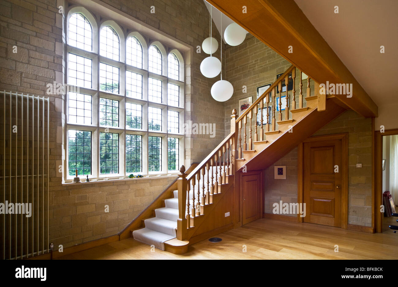 Grand wooden staircase and stone hallway with mullioned windows in a grand modern contemporary English house in - Stock Image