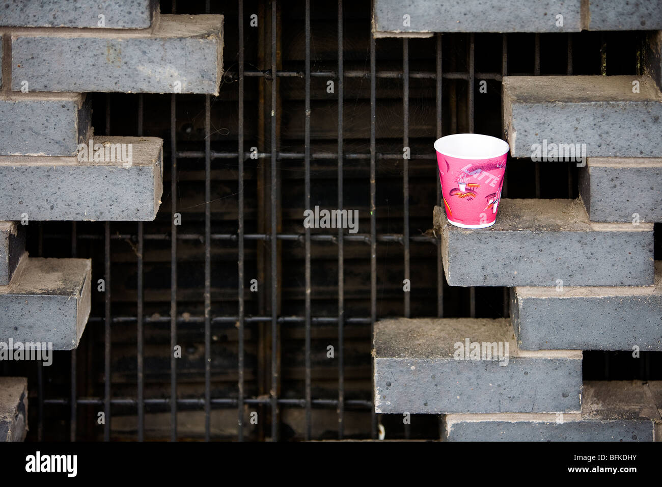 Empty red paper cup sits on the staggered opening in a brick wall at the side of The Lowry building - Stock Image