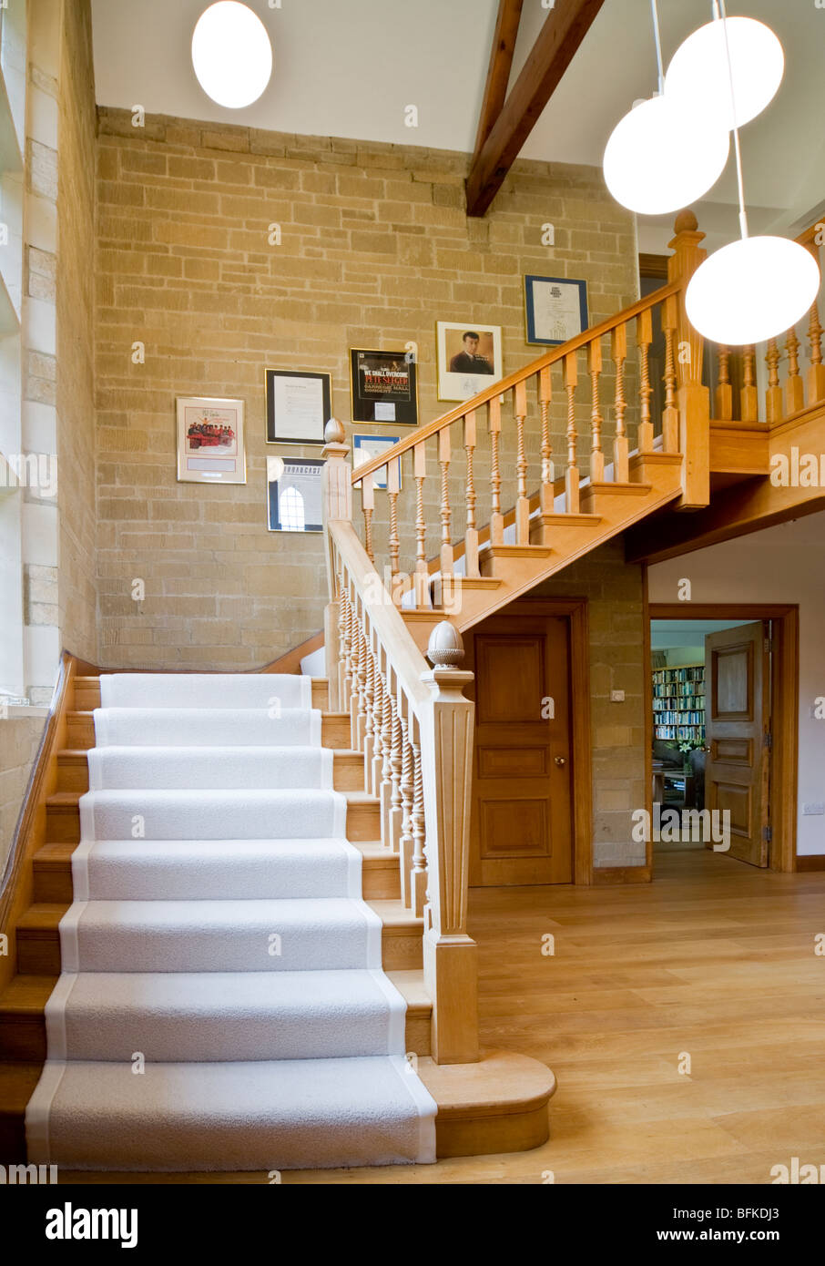 Grand wooden staircase and stone hallway in a grand modern contemporary English house in the UK - Stock Image