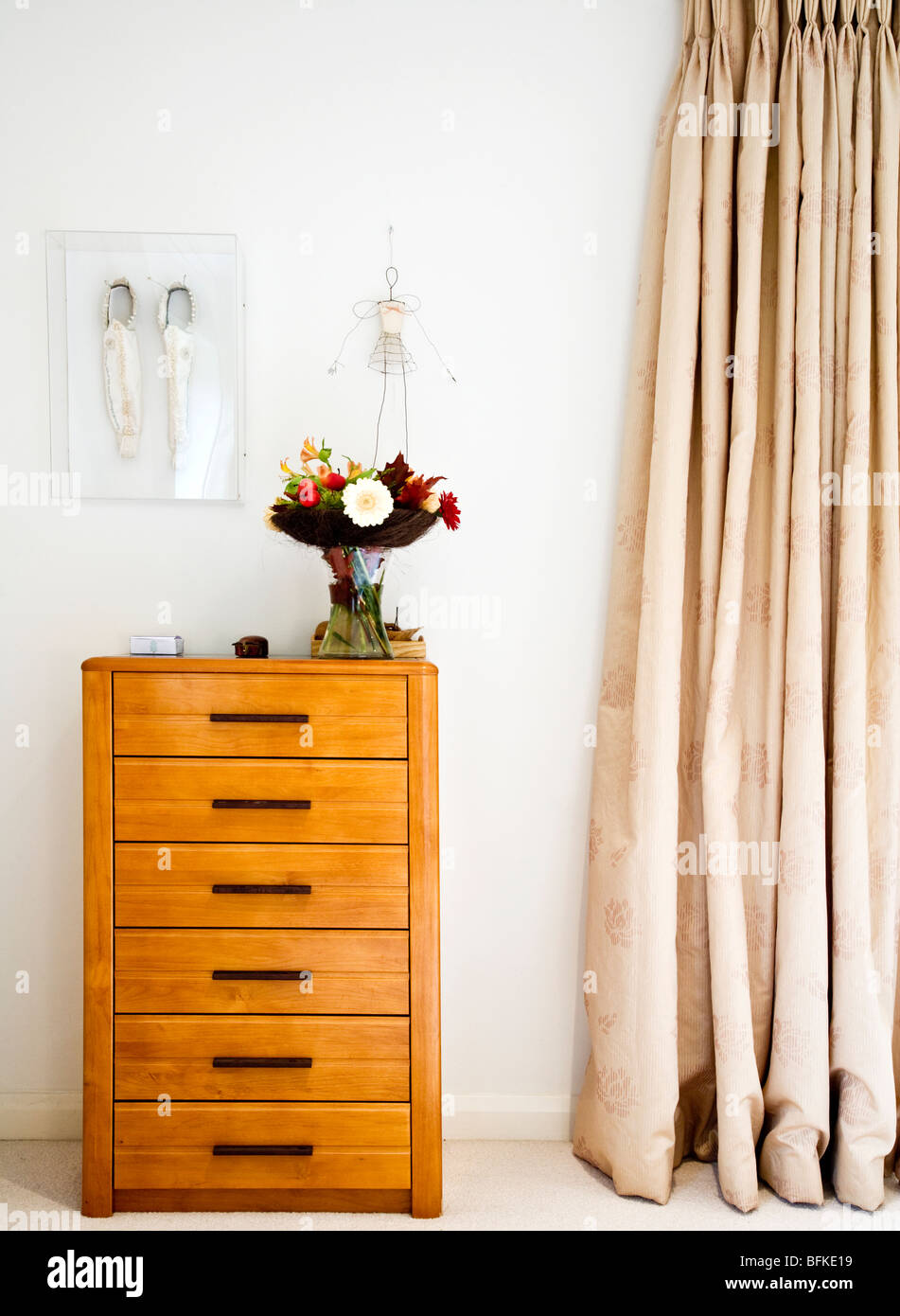 Chest of drawers or talboy on the corner of an English bedroom - Stock Image