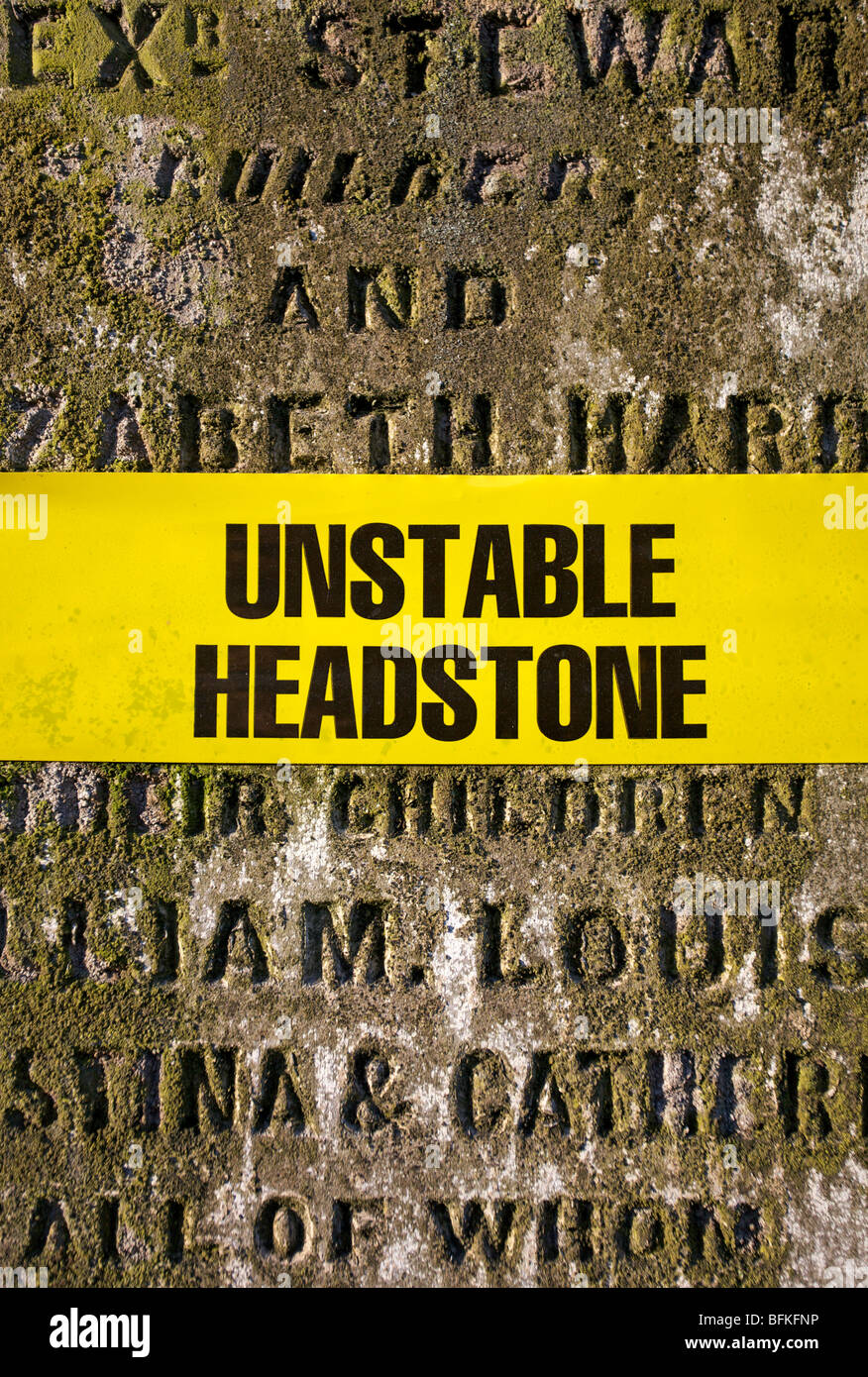 Unstable Headstone warning sign on an aged head stone in cemetery - Stock Image